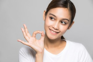 Young woman making OK hand sign.